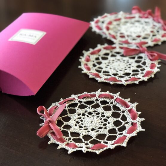 Lovely crochet coatsers with pink ribbon and a gift box.